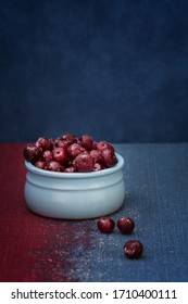 Cherry in a blue bowl on a blue background