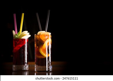 Cherry bomb and cuba libre cocktails in a tall glasses on the dark background. Shallow DOF