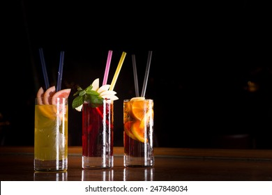 Cherry bomb, screwdriver and cuba libre cocktails in a tall glasses on the dark background. Shallow DOF