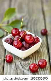 Cherry in a bowl on grey wooden old table. Ripe ripe cherries. Sweet red cherries.