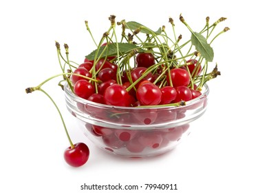 a cherry with a branch lies near a dish with a cherry