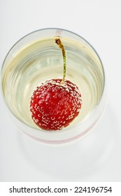 Cherry and bubbles in champagne glass, high angle view
