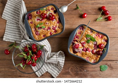 Cherry clafouti in portional ceramic forms on rustic wooden background. Homemade cake