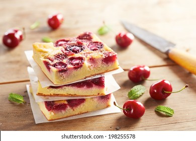 Cherry clafoutis pie portions stacked on wooden table