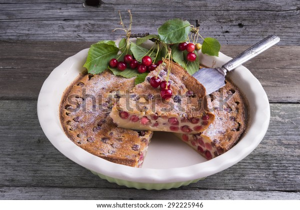 Cherry Clafoutis, traditional French dessert. Baked batter pudding with cherries, sprinkled with icing sugar and decorated with fresh cherries.