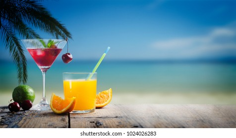 Cherry cocktail in martini glass and orange juice vodka on tropical sandy beach. Summer vacation holiday and beach party design. Island resort beach bar background.