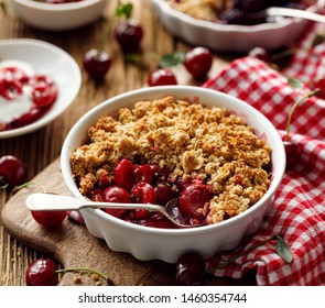 Cherry crumble, stewed fruits topped with crumble of oatmeal, almond flour, butter and sugar  in a baking dish on a wooden table, close-up