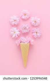 cherry flowers in a ice cream waffle cone on pink background