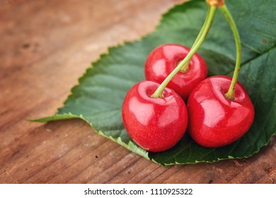 Cherry - Heap of berries on wood.  A pile of cherries and leaves
