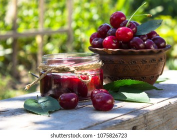 cherry jam in glass jar on garden openair