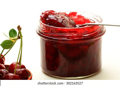 cherry jam in a jar on a white background