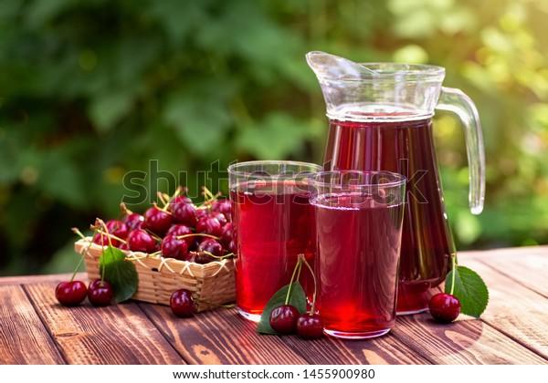 Kirschsaft in Gläsern und Saft mit reifen Beeren auf Holztisch im Freien. Erfrischungsgetränk im Sommer