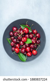 Cherry with leaf on plate and water dropsand on grey stone table. Ripe ripe cherries. Sweet red cherries. Top view. Rustic style. Fruit Background