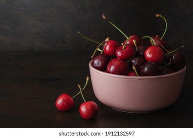 Cherry with leaf on plate and water dropsand on grey stone table. Ripe ripe cherries. Sweet red cherries.