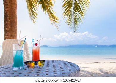 Cherry and lemon cocktail set on table  on tropical sandy beach. Summer vacation holiday and beach party design. Island resort beach bar background.