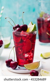 Cherry Limeade, lemonade, cola, cocktail in a tall glass on a white, turquoise background Copy space