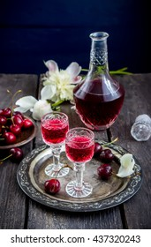 Cherry  liquor in glasses  and vintage bottle on metal tray. Wooden background, selective focus.