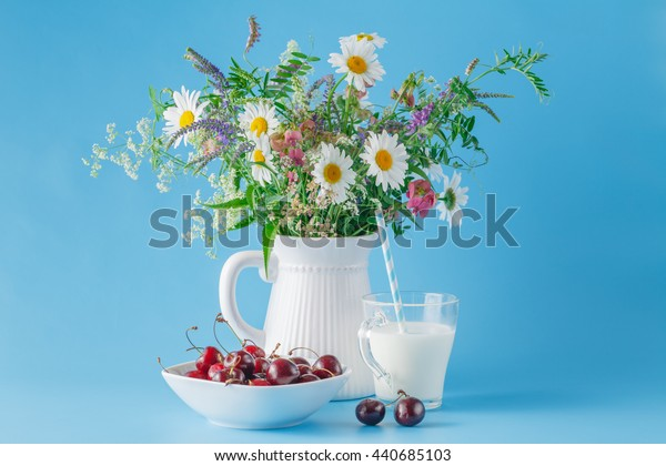 Cherry on plate with yogurt and wildflowers. blue background