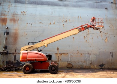 cherry picker in poor condition orange color look form side view.