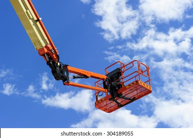 Cherry picker work bucket platform and hydraulic construction cradle of lifting arm painted in orange and beige colors with white clouds and blue sky on background, heavy industry machinery vehicle
