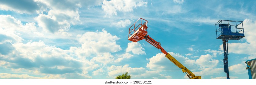 Cherry pickers on blue sky background. Boom with lift buckets of heavy machinery. Panoramic view of the platforms of the telescopic construction lifts in summer.