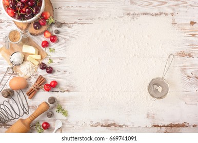 Cherry pie baking ingredients: fresh cherries, flour, egg, cinnamon, roller pin on a rustic white table. Background layout with free text space. Top view, flat lay style