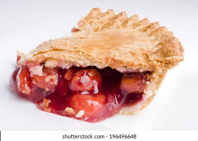Cherry pie with filling spilling out of the flaky crust.