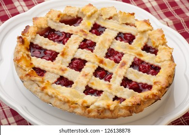 Cherry pie with lattice top on fall themed napkin, and mini pumpkins.