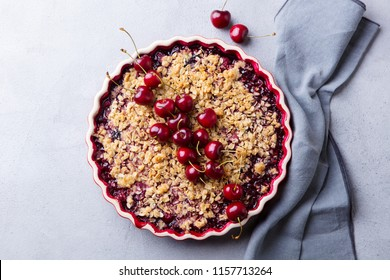 Cherry, red berry crumble in baking dish. Grey stone background. Top view.