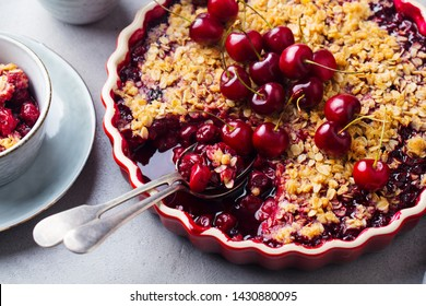 Cherry, red berry crumble in baking dish. Grey stone background. Close up.