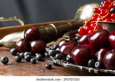 cherry with red currants and blueberries in a jug and a metal plate in oriental style on a background of wood