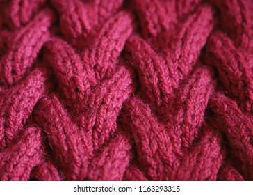Cherry Red warm wool, knitted texture. Handmade knitting with ornament as a background. Sweater Textile Background. Macro Closeup.
