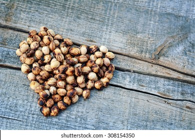 Cherry seeds on wooden background - Heart shape made of cherry seeds