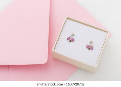 Cherry shaped earrings with crystals in gift box on pink envelope background with copy space. Cute jewelry for child girl. Present for birthday