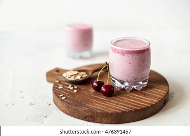 Cherry smoothie in glass on a cutting Board on a light background
