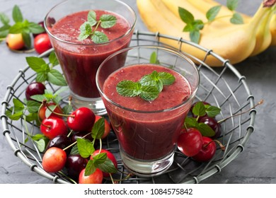 cherry smoothies in a glass on a gray concrete background