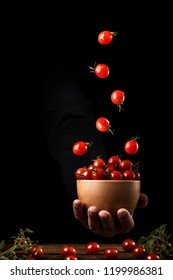 Cherry tomato flying on a wooden  bowl. Food in motion. Flying ingredients