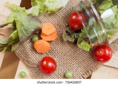 Cherry tomato and lettuce with the jar on a wooden table