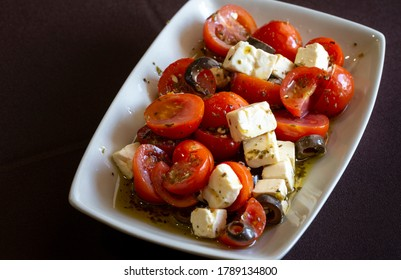 Cherry tomato salad with feta cheese, olives, and aromatic herbs.
