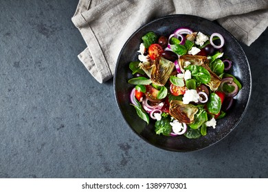 Cherry tomato and spinach salad with artichoke hearts, kalamata olives and feta cheese. Mediterranean cuisine. Flat lay
