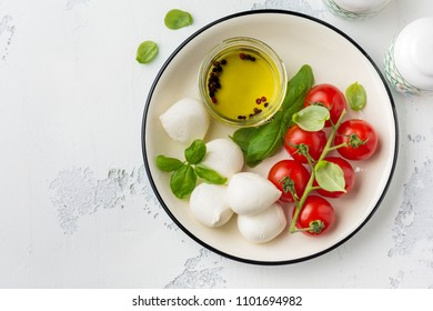 Cherry tomatoes, basil, mozzarella cheese and olive oil on white background. Italian food background. Top view.