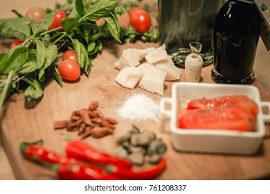 Cherry Tomatoes, basil and olive oil on wooden background, top view. Italian food cooking ingredients.