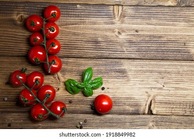 Cherry tomatoes and basil on rustic background - fresh cherry tomatoes on wooden table top view with copy space, horizontal orientation.