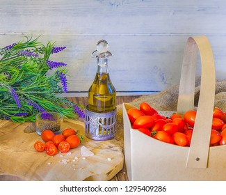 Cherry tomatoes in a cardboard  basket   with thyme,  olive oil , Himallayan pink salt on a wooden surface . Lavender flowers in the background. stock Image