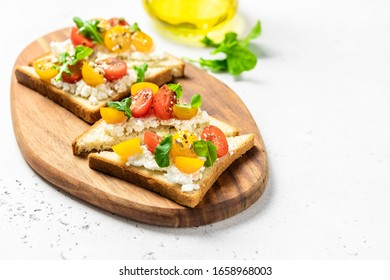 Cherry tomatoes cottage cheese toasts. Selective focus, copy space.
