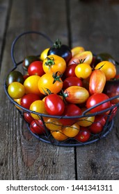 cherry tomatoes are different varieties in the basket, small tomatoes of different colors and types.