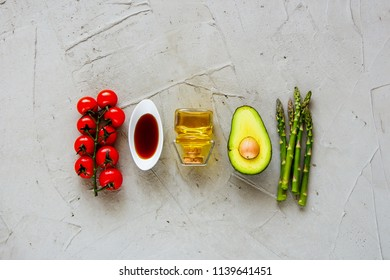 Cherry tomatoes, dressing, olive oil, avocado and aspargus flat lay. Healthy food clean eating selection. Cooking ingredients. Top view. Raw Bio Food on light background.
