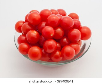 cherry tomatoes in glass bowl on white background