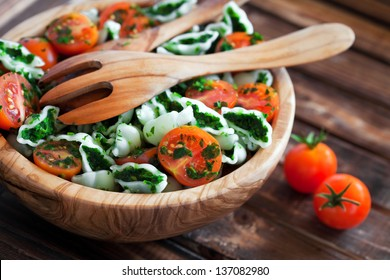 Cherry tomatoes with gluten-free pasta and spinach sauce, selective focus