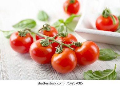 Cherry tomatoes and green fresh organic basil on wooden background